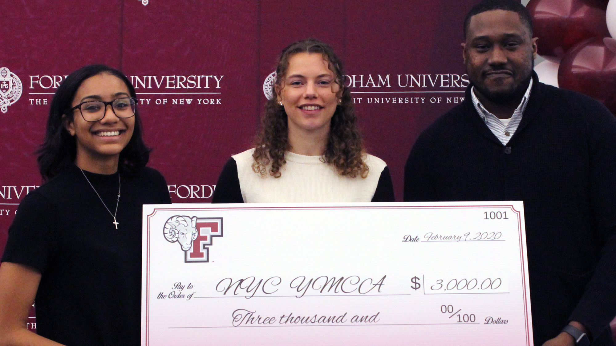 Members of SAAC present a check to the Harlem YMCA
